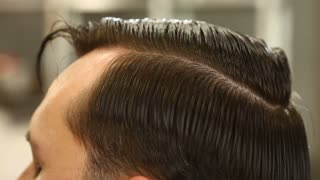 Barber smooths and combs wet hair of client