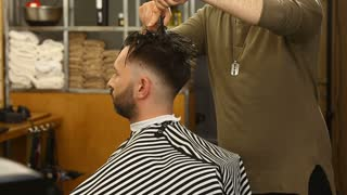 Profile of barber cutting wet Hair of client
