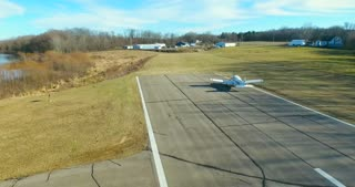 4K Aerial Following Small Plane Taxiing Down Runway Airplane At Airport Operated With Permission
