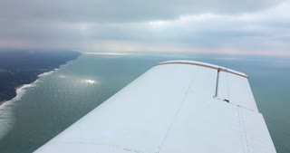 4K Small Airplane Flying Over Ice Lake Michigan Sun Rays Beechcraft Flying Aerial