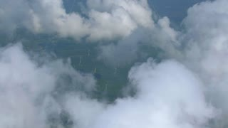 4K Aerial Windmills Renewable Energy Power Plant Paralax Through Clouds Airplane Flying