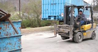 4K Metal Recycling Man Operating Fork Lift Carrying Metal Bin Away