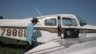 4K Pilot Climbing Into Small Airplane Beachcraft Musketeer Airport