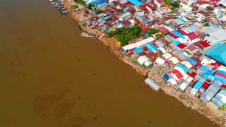 Aerial Phnom Penh Mekong River Comunity Pan Up To City Cambodia Crowded Streets Crime Human Trafficking Prostitute Urban Capitol City Buddhism Temple Pallace Tropical Palm Trees Flying View Footage South East Asian 4K