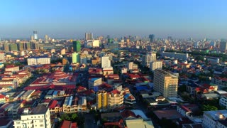 Aerial Phnom Penh Skyline Flyover Push In Traffic Streets Motorbike Vehicle Comunity City Cambodia Crime Human Trafficking Urban Capitol City Buddhism Tropical Palm Trees Flying Footage South East Asian 4K