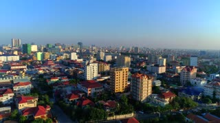Aerial Phnom Penh Skyline Orbit Traffic Streets Motorbike Vehicle Comunity City Cambodia Crime Human Trafficking Urban Capitol City Buddhism Tropical Palm Trees Flying Footage South East Asian 4K