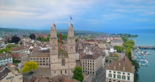 Aerial Zurich Switzerland Orbit Church Establishing Shot Europe Water River Lake Bridge Europe Steeple Architecture Tourist Destination View Swiss Town History Dark Ages Ulrich Zwingli Reformation Mideaval Fraumunster Grossmunster 4K