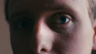 Slow Mo Intense Mans Eye Blinks And Looks Straight Into Camera Tight Eyeball Shot 4K