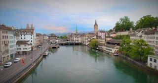 Zurich Switzerland Aerial Pull Back Up Establishing Shot Church Europe Water River Stream Statue Bridge Europe Steeple Walkway People Urban Architecture 4K 60 Fps Tourist Destination View Swiss Town