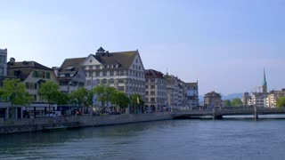 Zurich Switzerland Pan Right Establishing Shot Church Clock Tower Clocktower Europe Water River Stream Statue Bridge Europe Steeple Walkway People Urban Architecture 4K 60 FPS