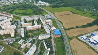 Aerial view of apartment buildings and road crossing slovak town Zvolen surrounded by green nature.