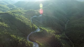 Aerial view of curvy road and forest during sunny summer day. Slovakia.