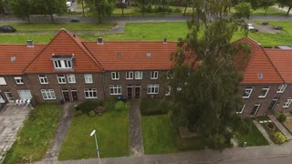 Aerial view of Dutch street with brick houses, cloudy sky. Netherlands