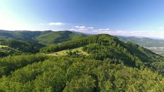 Aerial view of forest, grassland and village with houses during summer day. Slovakia, Nova Bana.
