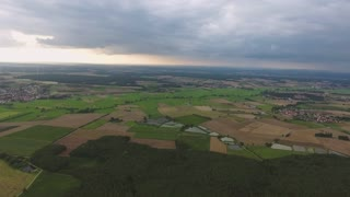 Aerial view of forests, fields, green grassland and villages during cloudy summer day. Netherlands