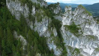 Aerial view of rocky hills with green trees, coniferous forest, village with houses. Mala Fatra, Slovakia.