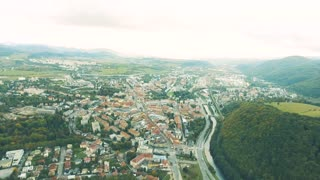 Aerial view of slovak town Banska Bystrica surrounded by mountains. Highway and river passing through the town.
