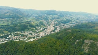 Aerial view of small town surrounded with many hills and forest. Slovakia, Nova Bana.