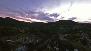 Aerial view of small town with many hills and forests surrounding it at dusk. Slovakia, Nova Bana.