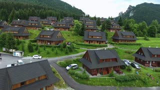 Aerial view of wooden cottages in the middle of green forest. Rocky hills of Mala Fatra, Slovakia.