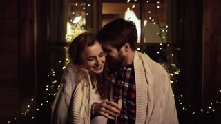 Beautiful hipster couple celebrating the end of the year, having party on New Years Eve, standing outside, wrapped in knitted blanket