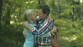 Beautiful senior woman and man on a walk in sunny summer forest. Hugging, kissing, touching noses.