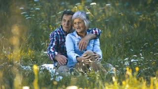 Beautiful senior woman and man sitting on sunny summer meadow, resting. Man pointing at something with his finger.