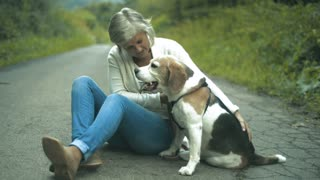 Beautiful senior woman on a walk with her beagle dog, sitting on a country road. Green sunny summer nature.