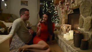 Beautiful young couple sitting on the floor in front of fireplace, drinking red wine.