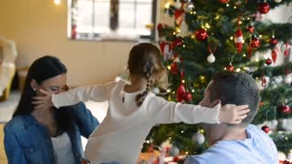 Beautiful young family with little daughter at decoratied Christmas tree at home, hugging.