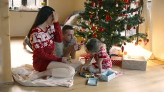 Beautiful young family with little daughter with many presents at Christmas tree at home.
