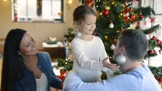 Beautiful young family with little girl decorating Christmas tree at home. Daughter giving her mother and father Christmas ornaments on her ears.