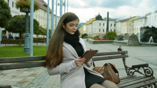 Beautiful young woman in autumn coat sitting on bench, working on tablet, outdoors in old town