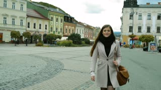 Beautiful young woman in autumn coat walking outdoors in old town