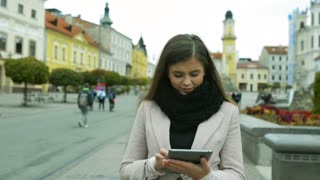 Beautiful young woman with tablet in autumn coat walking outdoors in old town