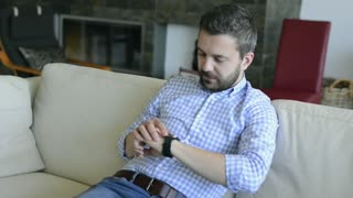 Casual man using smart watch, sitting on the sofa in living room