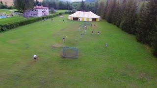 Children in summer camp playing football. Green summer nature. Forest, grassland, fields.