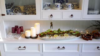 Christmas meal - trout with mayonnaise salad - laid on decorated white vintage cupboard with old service for coffee or tea with blue floral patter