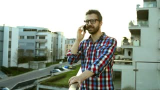 Hipster businessman in checked shirt with smart phone making a phone call, standing on balcony