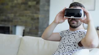 Hipster man in t-shirt wearing virtual reality goggles. Studio shot on white couch