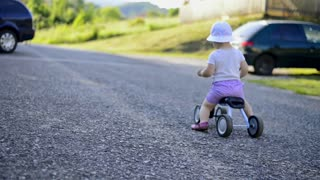 Litle girl riding a bicycle outside on country road, sunny summer day outdoors
