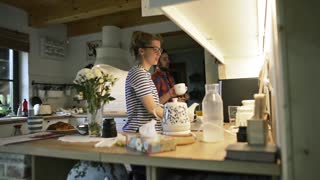 Man and woman in the kitchen, preparing drinks, cofee, normal day, everyday life