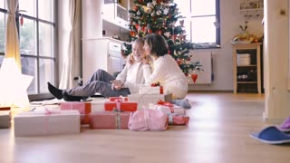 Senior couple sitting on the floor in front of illuminated Christmas tree inside their house, talking and laughing. Christmas presents all around them. Man entangled in chain of lights.