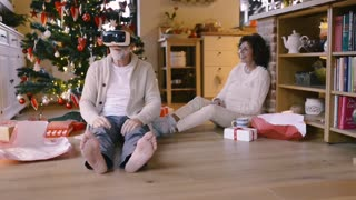 Senior couple sitting on the floor in front of illuminated Christmas tree inside their house unpacking presents.