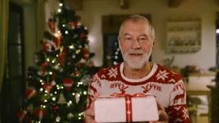 Unrecognizable senior man standing in front of illuminated Christmas tree inside in his house giving present to someone.