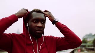 A black man runner with smartwatch and earphones putting hood on his head in a city. Slow motion.