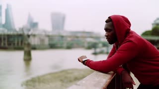 A black man runner with smartwatch, earphones and hood on his head standing in a city, listening to music. Slow motion. Copy space.