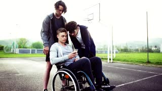 A boy in wheelchair and his teenager friends using a smartphone outdoors. Slow motion.
