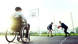 A boy in wheelchair with two teenager friends playing basketball outside at sunset. Slow motion.