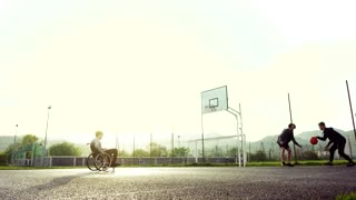 A boy in wheelchair with two teenager friends playing basketball outside at sunset.